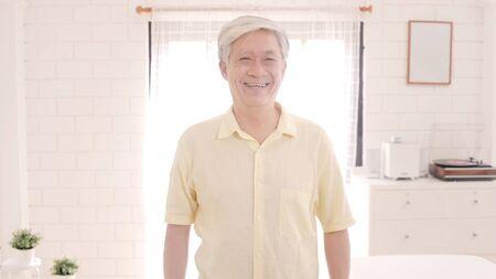 Asiatischer älterer Mann, der glücklich lächelt und auf die Kamera schaut, während er sich zu Hause auf dem Sofa im Wohnzimmer entspannt. Lifestyle-Senior-Männer zu Hause Konzept. Standard-Bild