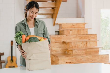 Asian women holding grocery shopping paper bags at home, young Asia girl happy buy vegetables and fruit healthy and organic product  from supermarket put it in kitchen in the morning concept.