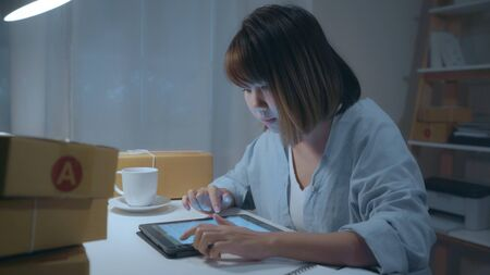 Beautiful smart Asian young entrepreneur business woman owner of SME online checking product on stock and save to tablet working late in night at home. Small business owner at home office concept.