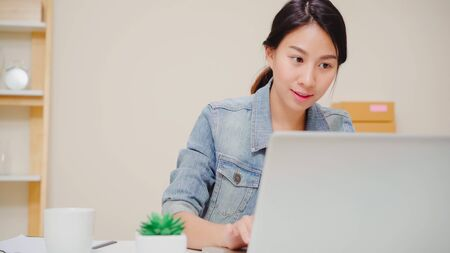Beautiful smart Asian young entrepreneur business woman owner of SME online checking product on stock and save to computer working at home. Small business owner at home office concept.