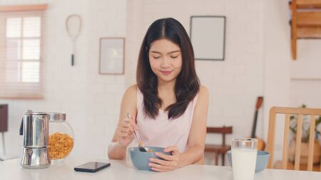 Asian Japanese woman has breakfast at home. Young Asia girls feeling happy drink juice, corn flakes cereal and milk in bowl on table in the kitchen in the morning concept.