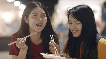 Asian young women friends travel in Bangkok, Thailand, beautiful female feeling happy walking and eating Pad Thai at The Khao San Road. Women travel eat street food in Thailand concept.