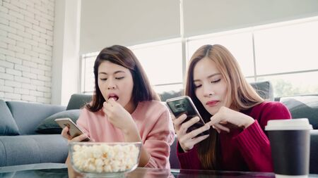 Asian women using smartphone and eating popcorn in living room at home, group of roommate friend enjoy funny moment while lying on the sofa. Lifestyle women relax at home concept. Фото со стока