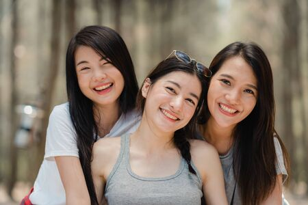 Teenage Asian female happy smiling to camera, Group of young Asian friends camping or picnic together in forest. Women do adventure activity and travel on holidays vacation in summer.