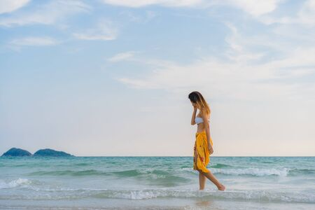 Beautiful young Asian woman happy relax walking on beach near sea. Lifestyle women travel on beach concept.