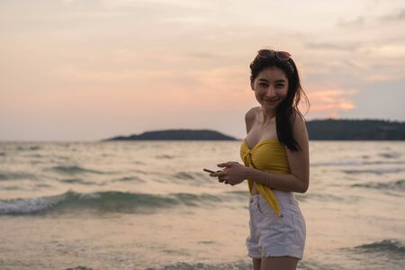 Asian teenage woman walking on beach. Beautiful girl using mobile phone checking social media near sea while enjoy her summer holiday vacation when sunset in evening. Фото со стока