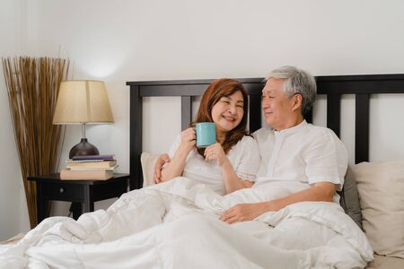 Asian senior couple talking on bed at home. Asian Senior Chinese grandparents, husband and wife happy drink coffee after wake up while lying on bed in bedroom at home in the morning concept.