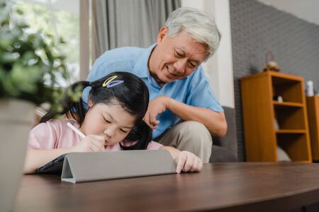 Asian grandfather teach granddaughter drawing and doing homework at home. Senior Chinese, grandpa happy relax with young girl lying on sofa in living room at home concept. Stockfoto