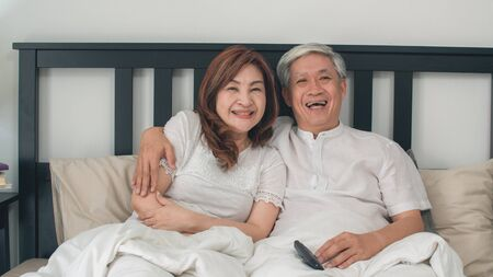 Asian elderly couple watching television in bedroom at home, Asia couple enjoy love moment while lying on the bed when relaxed at house. Enjoying time lifestyle senior family concept.