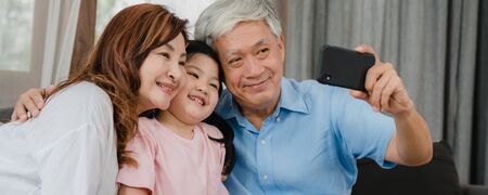 Asian grandparents selfie with granddaughter at home. Senior Chinese happy spend family time relax using mobile phone with young girl kid lying on sofa in living room. Panoramic banner background. Stockfoto