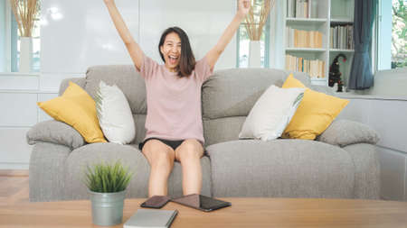Young Asian teenager woman watching TV at home, female feeling happy lying on sofa in living room. Lifestyle woman relax in morning at home concept.