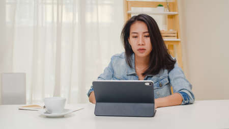 Frustrated Young Asia lady having problem with not working tablet computer sitting on desk. Freelance smart business women casual wear using tablet working in workplace in living room at home office.