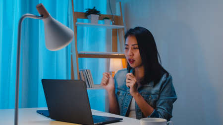 Freelance smart business women listening music after use laptop work hard in workplace in living room at home at night. Happy young Asian girl sitting on desk work overtime, dance enjoy relax time.