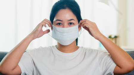 Depressed Asian business woman wearing protective mask sitting on sofa in living room at house when social distancing stay at home and self quarantine time Reklamní fotografie