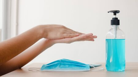 Asian woman using alcohol gel hand sanitizer wash hand before wear mask for protect coronavirus. Female push alcohol to clean for hygiene when social distancing stay at home and self quarantine time. Stok Fotoğraf