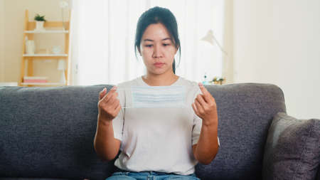 Depressed Asian business woman wearing protective mask sitting on sofa in living room at house when social distancing stay at home