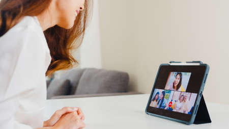 Young Asian business female using tablet video call talking with family while working from home at living room. Self-isolation, social distancing, quarantine for coronavirus in next normal concept. 写真素材