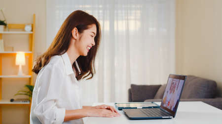 Young Asian business female using laptop video call talking with family dad and mom while working from home at living room. Self-isolation, social distancing, quarantine for coronavirus prevention. 写真素材