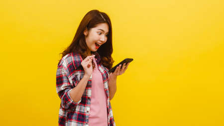 Portrait of surprised Asian female using mobile phone with positive expression, dressed in casual clothing and looking at camera over yellow background. Happy adorable glad woman rejoices success.