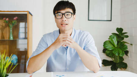 Young Asia businessman using computer laptop talk to colleagues about plan in video call meeting while working from home at living room. Self-isolation, social distancing, quarantine for corona virus.