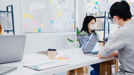 Asia businesspeople entrepreneur wearing medical face mask for social distancing in new normal situation for virus prevention while using laptop back at work in office. Lifestyle after corona virus. Standard-Bild