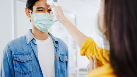 Asia female receptionist conducting wear protective face mask use infrared thermometer checker or temperature gun on customer's forehead before enter office. Lifestyle new normal after corona virus.