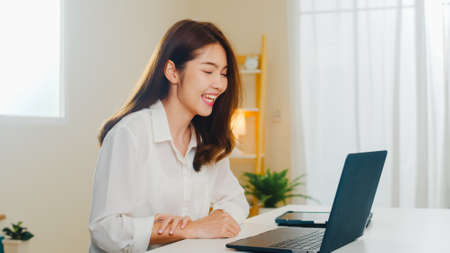 Young Asian business female using laptop video call talking with couple while working from home at living room. Self-isolation, social distancing, quarantine for coronavirus in next normal concept.