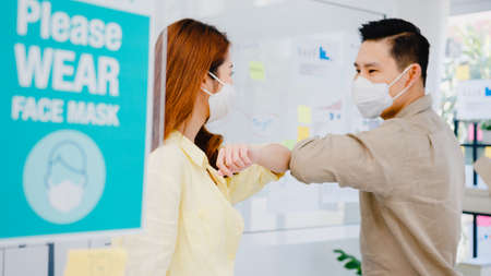 Asia businesspeople greeting with elbow bump and wear medical face mask for social distancing in new normal situation for virus prevention back at work in office. Lifestyle and work after coronavirus. Standard-Bild