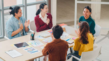 Multiracial group of Asia young creative people in smart casual wear discussing business clapping, laughing and smiling together in brainstorm meeting at office. Coworker teamwork successful concept. Standard-Bild