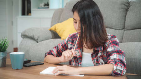 Asian student woman do homework at home, female using tablet for searching on sofa in living room at home. Lifestyle women relax at home concept.