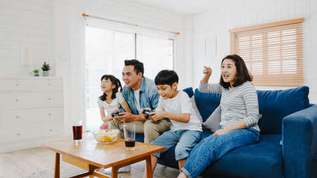 Happy Asia family dad, mom and kids funny playing video game with technology console in living room at house. Self-isolation, stay at home, social distancing, quarantine for coronavirus prevention.