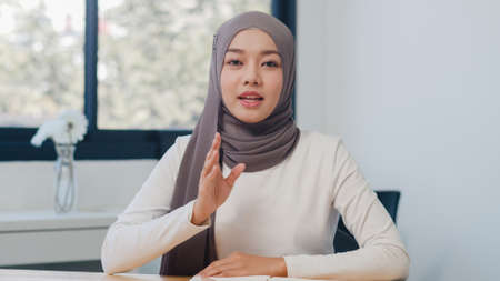 Asia muslim lady looking at camera talk to colleagues about plan in video call in new normal office. Working from home, remotely work, self isolation, social distancing, quarantine for coronavirus.