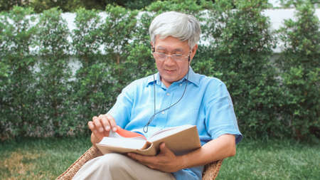 Asian senior men relax at home. Asian Senior Chinese male enjoy rest time wear glasses read books while lying in the garden at home in the morning concept. Foto de archivo