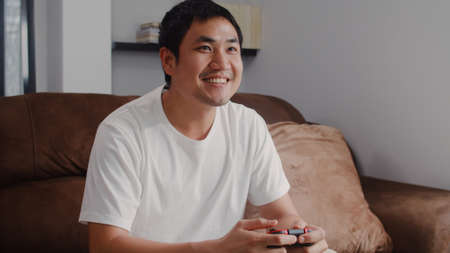 Young Asian man using joystick playing video games in television in living room, male feeling happy using relax time lying on sofa at home. Men play games relax at home concept.