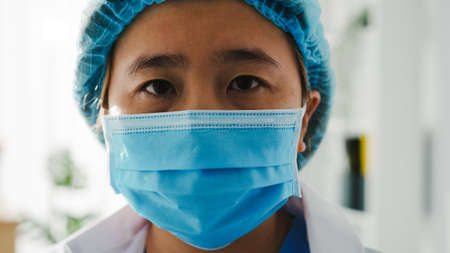 Young Asia lady doctor or nurse worker surgeon preparing for surgical operation and tired opens eyes and looking at camera at health hospital office. Social distancing, quarantine for virus.