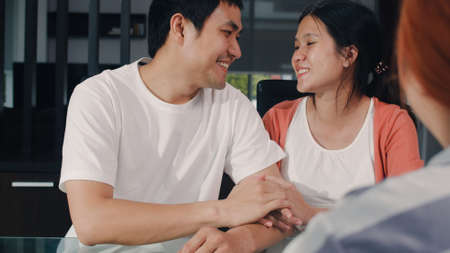 Young Asian Pregnant couple sign contract documents at home, Japanese family consulting with real estate financial advisor, Buying new house and handshaking with broker in living room in the morning.