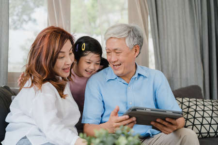 Asian grandparents and granddaughter using tablet at home. Senior Chinese, grandpa and grandma happy spend family time relax with young girl checking social media, lying on sofa in living room concept Imagens