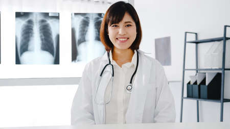 Confident young Asia female doctor in white medical uniform with stethoscope looking at camera and smiling while video conference call with patient in health hospital. Consulting and therapy concept.