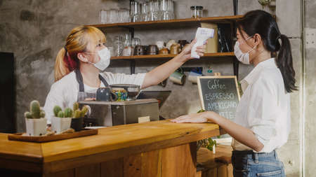 Young Asia female restaurant staff wearing protective face mask using infrared thermometer checker or temperature gun on customer's forehead before enter. Lifestyle new normal after pandemic