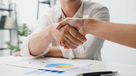 Multiracial group of young creative people in smart casual wear discussing business shaking hands together and smiling while sitting in modern office. Partner cooperation, coworker teamwork concept.