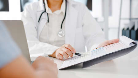 Young Asia female doctor in white medical uniform using clipboard is delivering great news talk discuss results or symptoms with male patient sitting at desk in health clinic or hospital office.