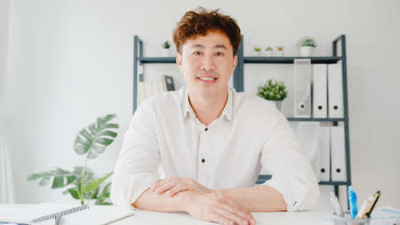 Young Asia businessman using computer laptop talk to colleagues about plan in video call meeting while working from home at living room. Self-isolation, social distancing, quarantine for virus.