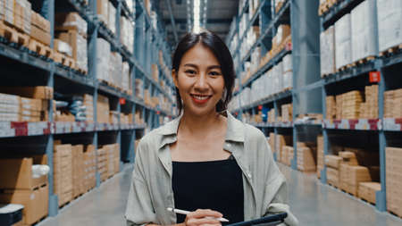 Portrait of attractive young Asia businesswoman manager smiling charmingly looking at camera hold digital tablet stand in retail shopping center. Distribution, Logistics, Packages ready for shipment.