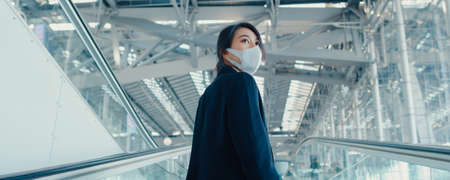 Asian business girl wear face mask drag luggage stand on escalator look around walk to terminal at international airport. Business travel social distancing concept. Panoramic banner background.