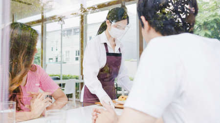 Young Asia female restaurant staff wearing protective face mask and gloves serving food to customer in cafe. Lifestyle new normal restaurant after  virus and social distancing concept.