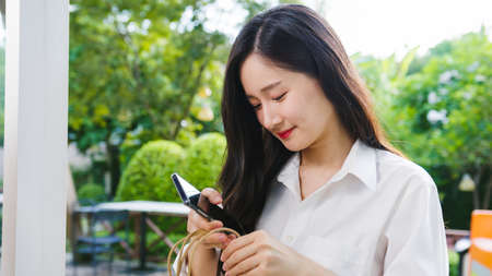 Young Asia businesswoman wearing medical face mask using mobile phone outside during virus health crisis in street in city. Lifestyle new normal after virus and social distancing