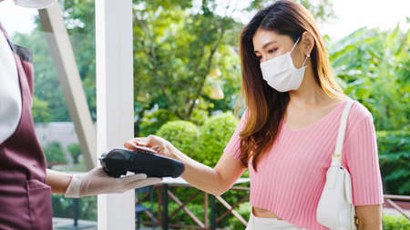 Young Asia female customer wear face mask making contactless credit card payment and take out food bag order from restaurant staff in coffee shop. Lifestyle new normal after corona virus concept.