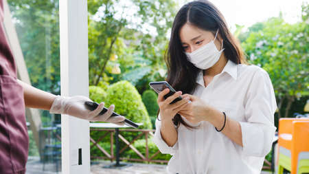 Young Asia female customer wear face mask making contactless mobile phone payment and take out food bag order from restaurant staff in coffee shop.
