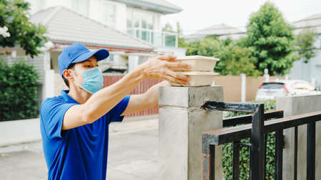 Young postal delivery courier man wear face mask handling food box for send to customer at house and Asian female receive delivered package outdoors.