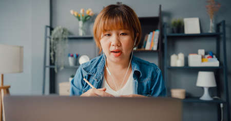 Asia businesswoman using laptop talk to colleagues about plan in video call while working from house at living room. Remotely at workplace, social distancing, quarantine for corona virus prevention.